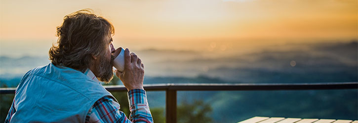 Man drinking coffee and watching the sunrise