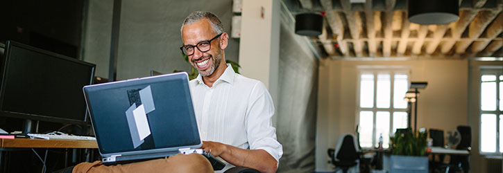 Business owner smiling on laptop