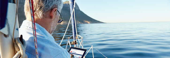 Man on a boat checks his finances on his iPad