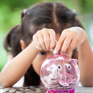 Little girl putting money inside piggy bank