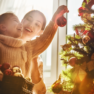 Mother and daughter hanging ornaments on a Christmas tree